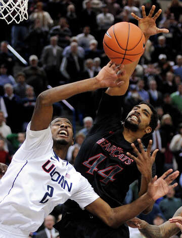 Connecticut's DeAndre Daniels, left, fights for a rebound with Cincinnati's JaQuon Parker during the second half of Connecticut's 73-66 overtime victory in an NCAA college basketball game in Hartford, Conn., Thursday, Feb. 21, 2013. (AP Photo/Fred Beckham) Photo: Fred Beckham, Associated Press / FR153656 AP