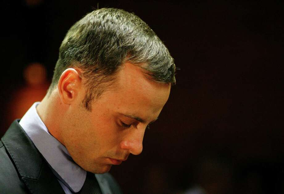 Olympic athlete Oscar Pistorius stands during his bail hearing at the magistrate court in Pretoria, South Africa, Thursday, Feb. 21, 2013. The lead investigator in the murder case against Pistorius faces attempted murder charges himself over a 2011 shooting, police said Thursday in another potentially damaging blow to the prosecution. Prosecutors said they were unaware of the charges against veteran detective Hilton Botha when they put him on the stand in court to explain why Pistorius should not be given bail in the Valentine's Day shooting death of his girlfriend. (AP Photo/Themba Hadebe) Photo: Themba Hadebe