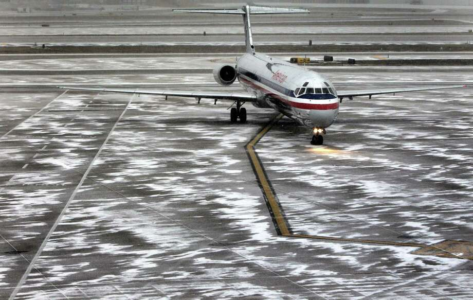 An American Airlines flight arrives as sleet falls at Lambert-St. Louis International Airport, on Thursday, Feb. 21, 2013. Blinding snow, at times accompanied by thunder and lightning, bombarded much of the nation's midsection Thursday. Freezing rain and sleet were forecast for southern Missouri, southern Illinois and Arkansas. St. Louis was expected to get all of the above — a treacherous mix of snow, sleet and freezing rain. (AP Photo/St. Louis Post-Dispatch, Robert Cohen)  EDWARDSVILLE INTELLIGENCER OUT; THE ALTON TELEGRAPH OUT Photo: Robert Cohen