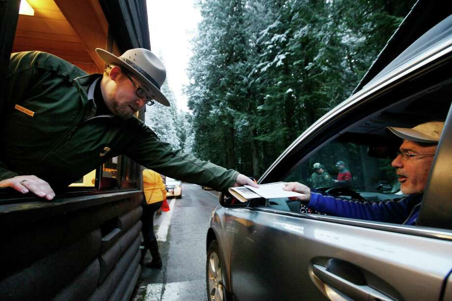 FILE - In this Jan. 7, 2012 file photo, Mount Rainier  National Park Ranger Matt Chalup, left, hands park information to one of the first visitors to the park at the Nisqually entrance near Ashford, Wash. The politics have been fierce and the fingerpointing incessant. Come March 1, the across-the-board federal spending cuts called sequestration go into effect, launching a new season of economic uncertainty for a nation still trying to shake off a recession. A look at the cuts, how much they amount to and who they will affect -- in question and answer form. (AP Photo/Elaine Thompson, File) Photo: Elaine Thompson