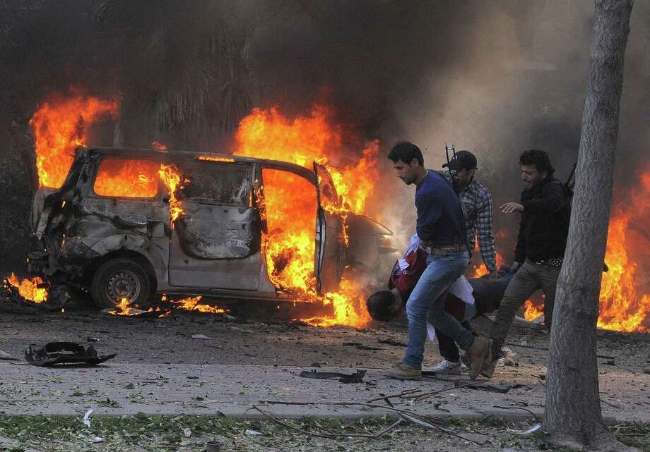 This photo released by the Syrian official news agency SANA, shows Syrian security agents carrying a body following a huge explosion that shook central Damascus, Syria, Thursday, Feb. 21, 2013. A car bomb shook central Damascus on Thursday, exploding near the headquarters of the ruling Baath party and the Russian Embassy, eyewitnesses and opposition activists said. (AP Photo/SANA) Photo: Anonymous