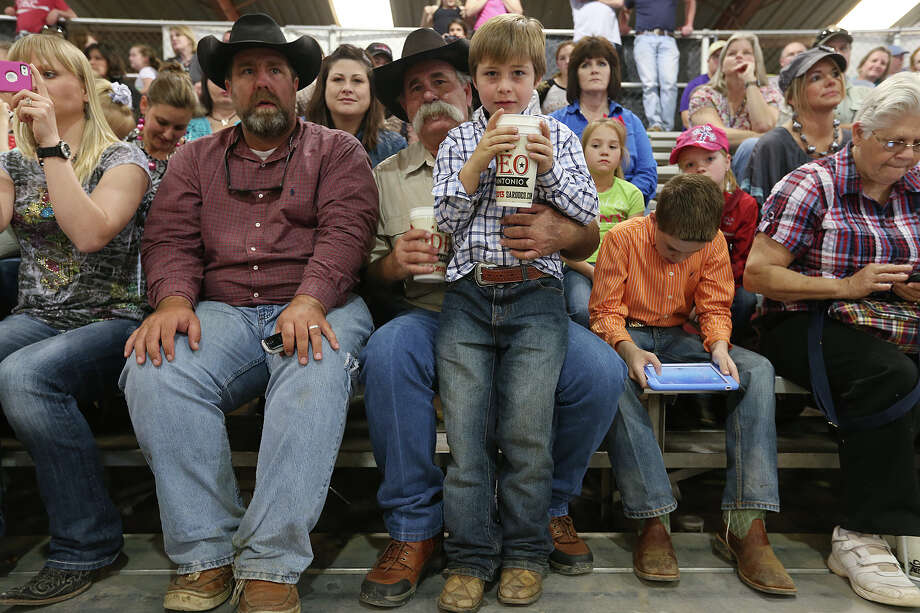 Holding his grandson, Rancher Jalufka, 7, former Karnes County Sheriff David Jalufka, 62, sits next to his son, Gabe Jalufka, 37, while watching steer judging at the San Antonio Stock Show and Rodeo, Thursday, Feb. 21, 2013. Jalufka spent three decades with the Department of Public Safety before being elected sheriff in 2004. Jalufka has seen the tremendous change the county has undergone with the demands brought on by Eagle Ford Shale play. Photo: Jerry Lara, San Antonio Express-News / © 2013 San Antonio Express-News