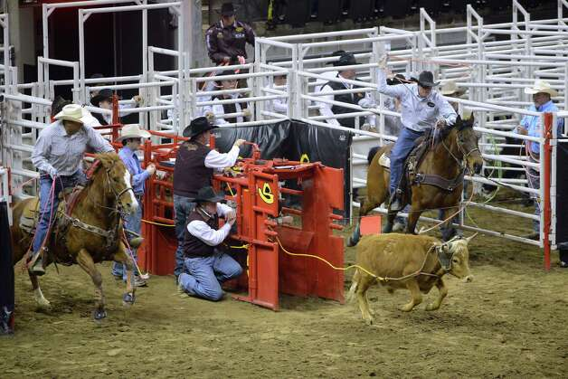 John Chaves, left, and Clay White compete in team roping during the San Antonio Stock Show & Rodeo in the AT&T Center on Thursday, Feb. 21, 2013. Photo: Billy Calzada, San Antonio Express-News / San Antonio Express-News