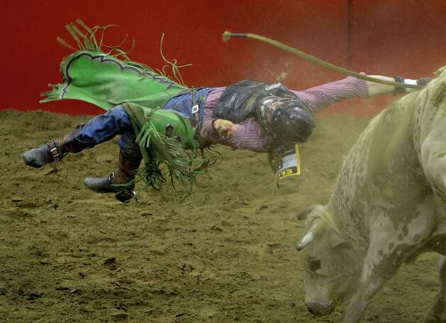 Competitor Jeff Askey is tossed during the bull riding event at the San Antonio Stock Show & Rodeo in the AT&T Center on Thursday, Feb. 21, 2013. Photo: Billy Calzada, San Antonio Express-News / San Antonio Express-News