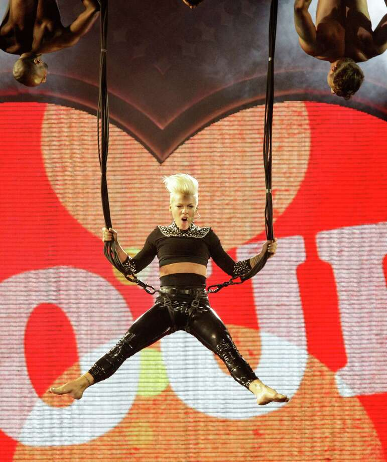 Singer Pink twirls around the air at the Toyota Center on Thursday night. Photo: Melissa Phillip, Staff / © 2013  Houston Chronicle