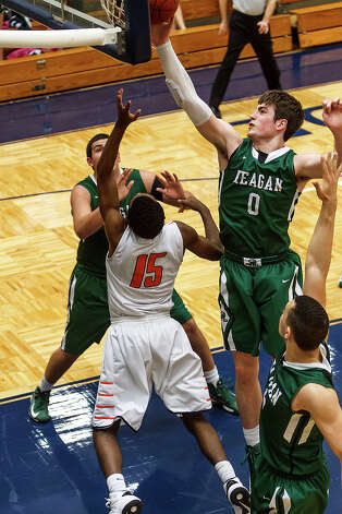 Reagan's D.J. MacLeay (right) blocks a layup by Brandeis's Justin Graham (15) during the first half of their Class 5A boys basketball second round game at Paul Taylor Field House on Thursday, Feb. 21, 2013. Brandeis won the game 64-58.  MARVIN PFEIFFER/ mpfeiffer@express-news.net Photo: MARVIN PFEIFFER, Express-News / Express-News 2013