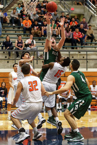 Reagan's D.J. MacLeay leaps over Brandeis's Justin Graham (15) for a rebound during the first half of  their Class 5A boys basketball second round game at Paul Taylor Field House on Thursday, Feb. 21, 2013. Brandeis won the game 64-58.  MARVIN PFEIFFER/ mpfeiffer@express-news.net Photo: MARVIN PFEIFFER, Express-News / Express-News 2013
