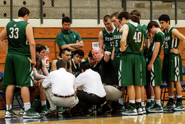 Reagan head coach John Hirst (center) points to a spot on the floor during a fourth quarter time out in their Class 5A boys basketball second round game with Brandeis at Paul Taylor Field House on Thursday, Feb. 21, 2013.  Brandeis won the game 64-58.   MARVIN PFEIFFER/ mpfeiffer@express-news.net Photo: MARVIN PFEIFFER, Express-News / Express-News 2013