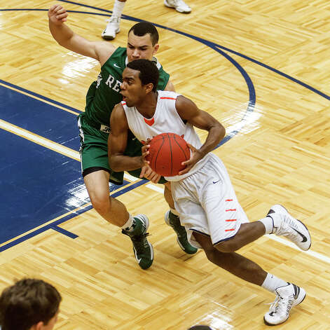 Brandeis's Justin Graham tries to drive to the basket past Reagan's Michael Williams during the first half of their Class 5A boys basketball second round game at Paul Taylor Field House on Thursday, Feb. 21, 2013. Brandeis won the game 64-58.  MARVIN PFEIFFER/ mpfeiffer@express-news.net Photo: MARVIN PFEIFFER, Express-News / Express-News 2013