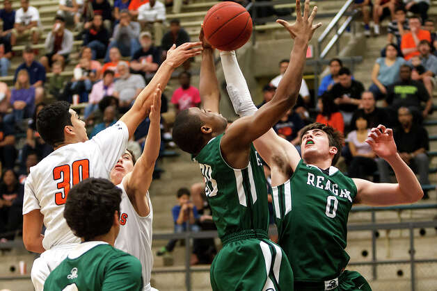 Reagan's D.J MacLeay (from right) and Chuck Kendley battle for a rebound with Brandeis's Matt Kallead during the firs half of their Class 5A boys basketball second round game at Paul Taylor Field House on Thursday, Feb. 21, 2013. Brandeis advanced with a 64-58 victory over the Rattlers.  MARVIN PFEIFFER/ mpfeiffer@express-news.net Photo: MARVIN PFEIFFER, Express-News / Express-News 2013
