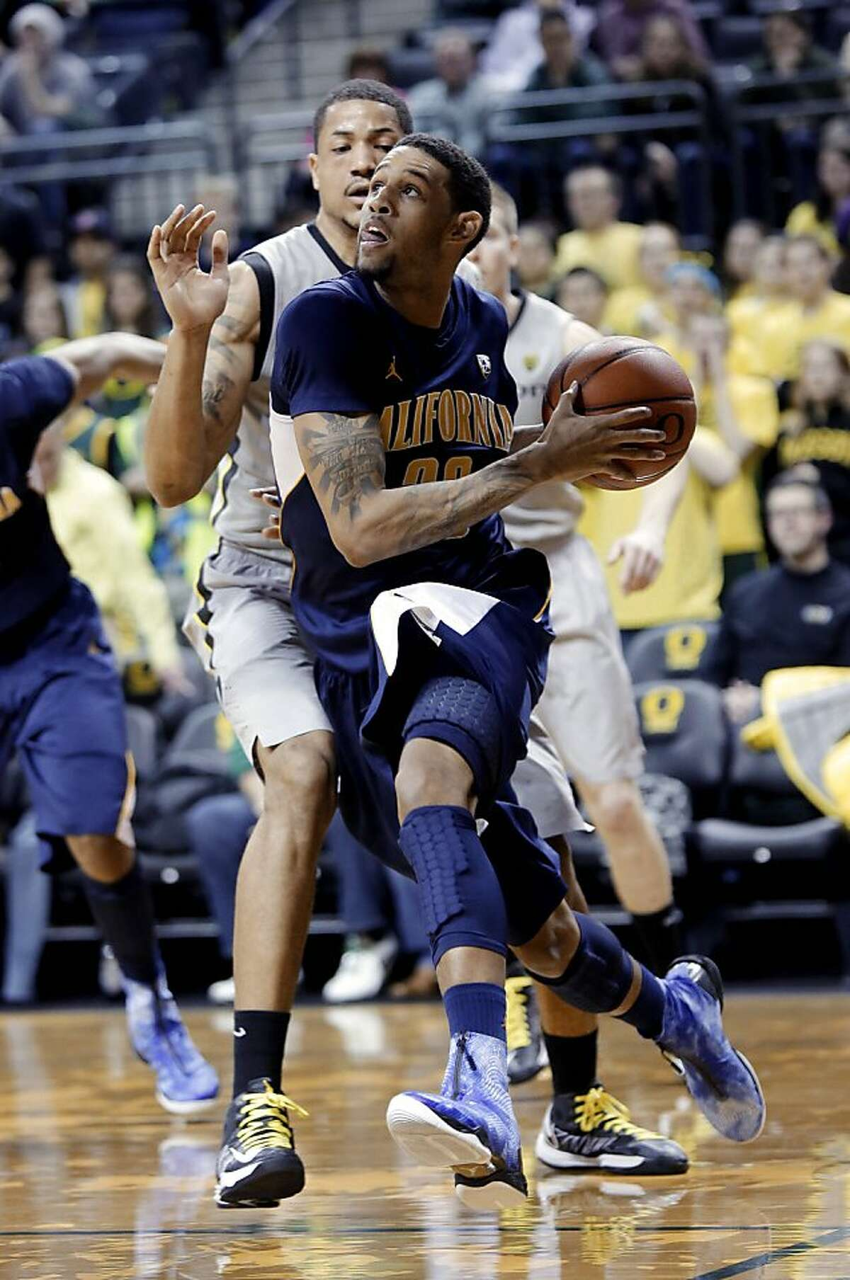 California guard Allen Crabbe, right, drives the baseline against Oregon center Tony Woods during the second half of an NCAA college basketball game in Eugene, Ore., Thursday, Feb. 21, 2013. Crabbe scored 12 points as California defeated Oregon 48-46. (AP Photo/Don Ryan)