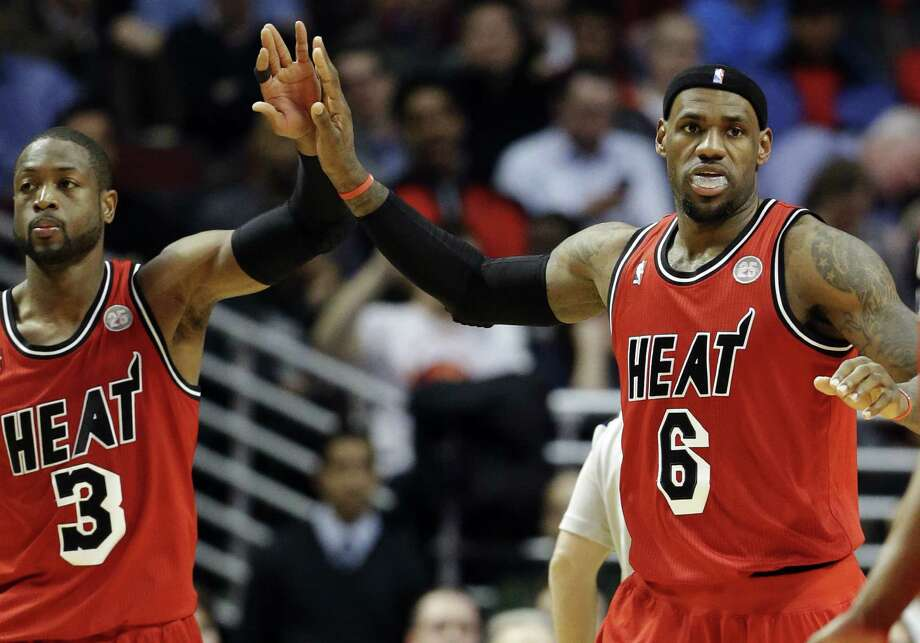 Dwyane Wade (left) and LeBron James share a high-five during the second half of the Heat's victory over the Bulls on Thursday in Chicago. James scored 26 points and Wade added 17. Photo: Nam Y. Huh / Associated Press