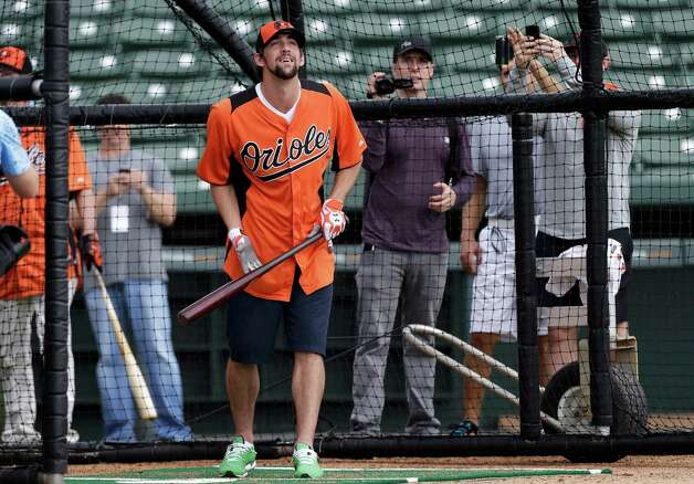 Former Olympic swimmer Michael Phelps watches a fly ball while hitting in the batting cage during a Baltimore Orioles baseball spring training workout Thursday, Feb. 21, 2013, in Sarasota, Fla.  Phelps, a native of Baltimore who was in the area filming his Golf Channel show The Haney Project, took batting practice with the team. (AP Photo/Charlie Neibergall) Photo: Charlie Neibergall