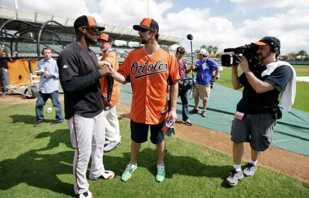 Former Olympic swimmer Michael Phelps talks with Baltimore Orioles center fielder Adam Jones, left, during a baseball spring training workout Thursday, Feb. 21, 2013, in Sarasota, Fla.  Phelps, a native of Baltimore who was in the area filming his Golf Channel show The Haney Project, took batting practice with the team. (AP Photo/Charlie Neibergall) Photo: Charlie Neibergall