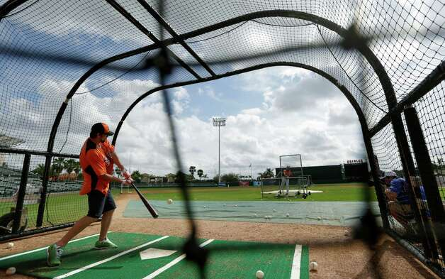 Former Olympic swimmer Michael Phelps hits in the batting cage during a Baltimore Orioles baseball spring training workout Thursday, Feb. 21, 2013, in Sarasota, Fla.  Phelps, a native of Baltimore who was in the area filming his Golf Channel show The Haney Project, took batting practice with the team. (AP Photo/Charlie Neibergall) Photo: Charlie Neibergall