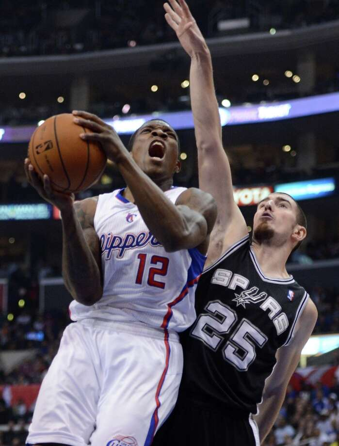 Eric Bledsoe #12 of the  Clippers attempts a shot in front of the defense of Nando de Colo #25 of the Spurs at Staples Center on February 21, 2013 in Los Angeles, California. Photo: Harry How, Getty Images / 2013 Getty Images