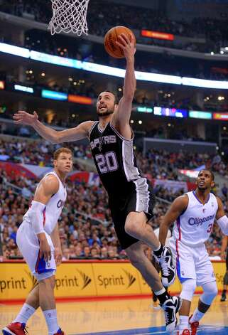 Spurs guard Manu Ginobili, center, goes up for a shot as Clippers forward Blake Griffin, left, and guard Chris Paul watch during the first half, Thursday, Feb. 21, 2013, in Los Angeles. Photo: Mark J. Terrill, Associated Press / AP