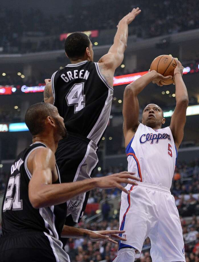Caron Butler #5 of the  Clippers attempts a shot in front of Danny Green #4 and Tim Duncan #21 of the Spurs at Staples Center on February 21, 2013 in Los Angeles, California. Photo: Harry How, Getty Images / 2013 Getty Images
