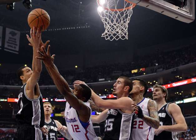 Danny Green #4 of the Spurs and Eric Bledsoe #12 of the Clippers reach for a rebound in front of Nando de Colo #25 at Staples Center on February 21, 2013 in Los Angeles, California. Photo: Harry How, Getty Images / 2013 Getty Images