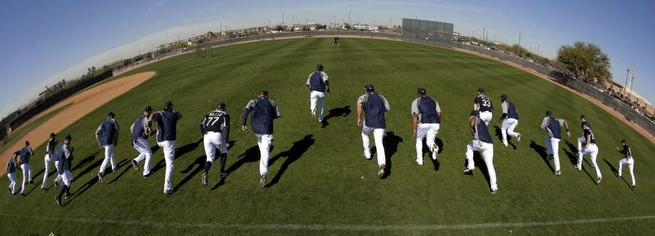 In this photo taken with a fisheye lens, Mariners position players run sprints during a spring training workout Tuesday in Peoria, Ariz.