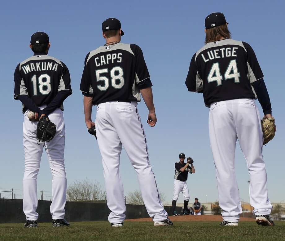 Mariners pitchers Hisashi Iwakuma (18), Carter Capps (58) and Lucas Luetge (44) watch while fellow pitcher Charlie Furbush throws during spring training Tuesday in Peoria, Ariz.
