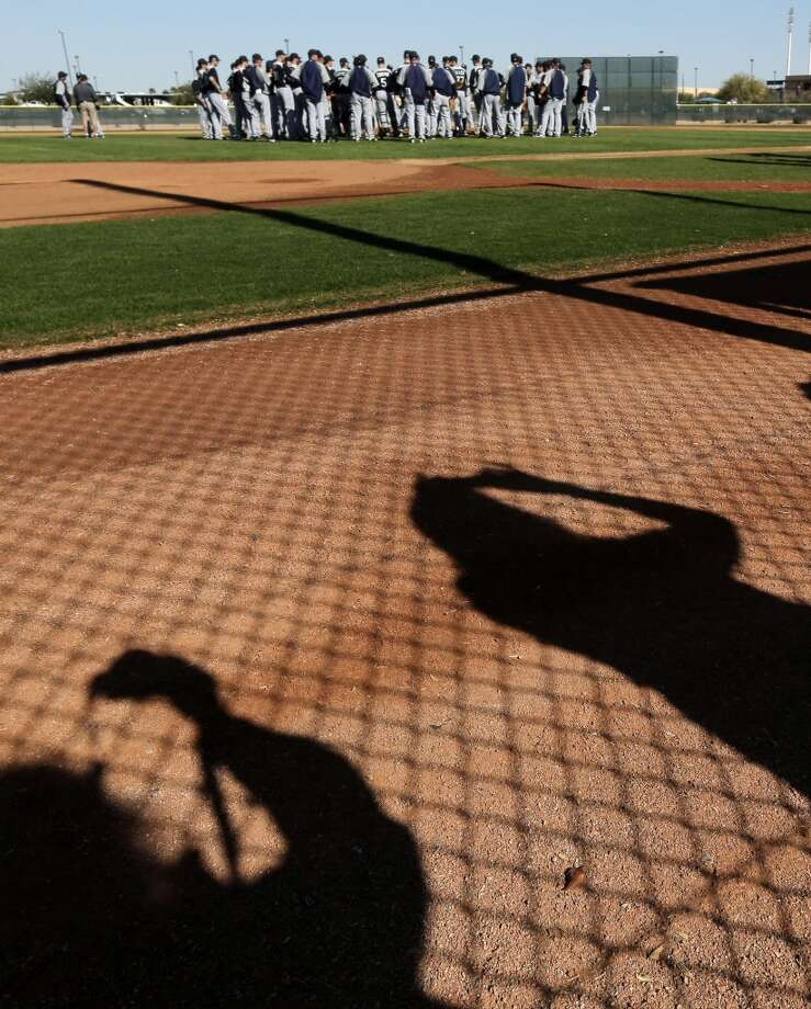 Fans take photos through a fence as Mariners players meet at the mound during a spring training workout Monday in Peoria, Ariz.