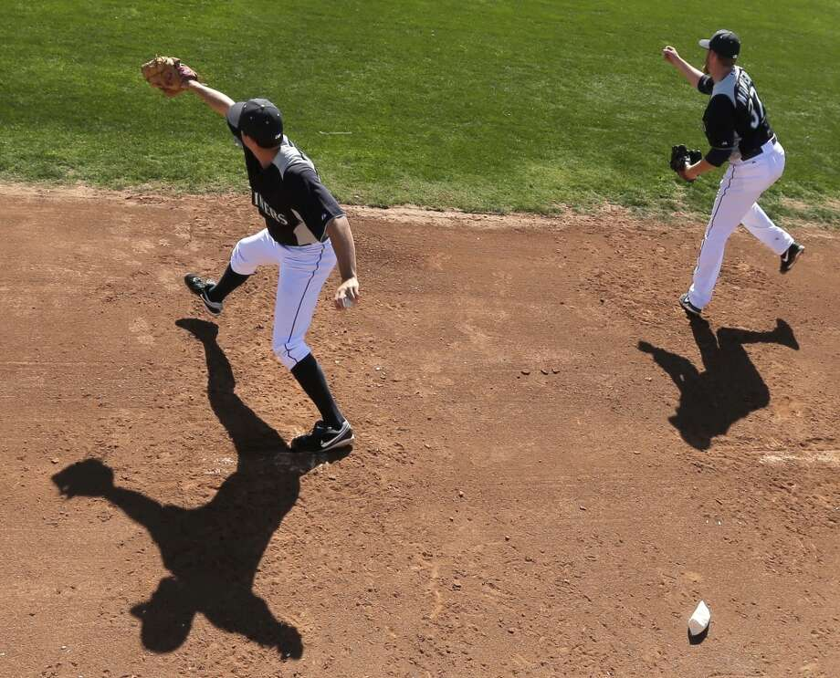 Mariners pitchers Danny Hultzen (left) and Brandon Maurer throw during spring training Tuesday in Peoria, Ariz.