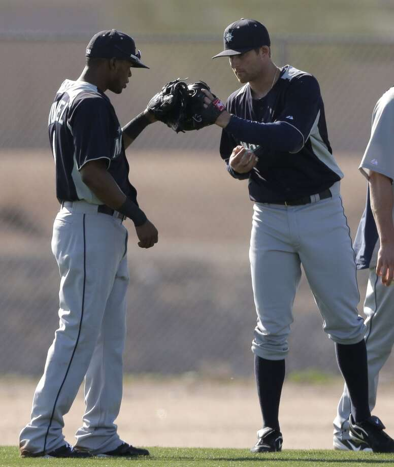 Mariners shortstop Carlos Triunfel (left) and catcher Brad Miller bump gloves after a participating in a drill during a spring training workout Monday in Peoria, Ariz.