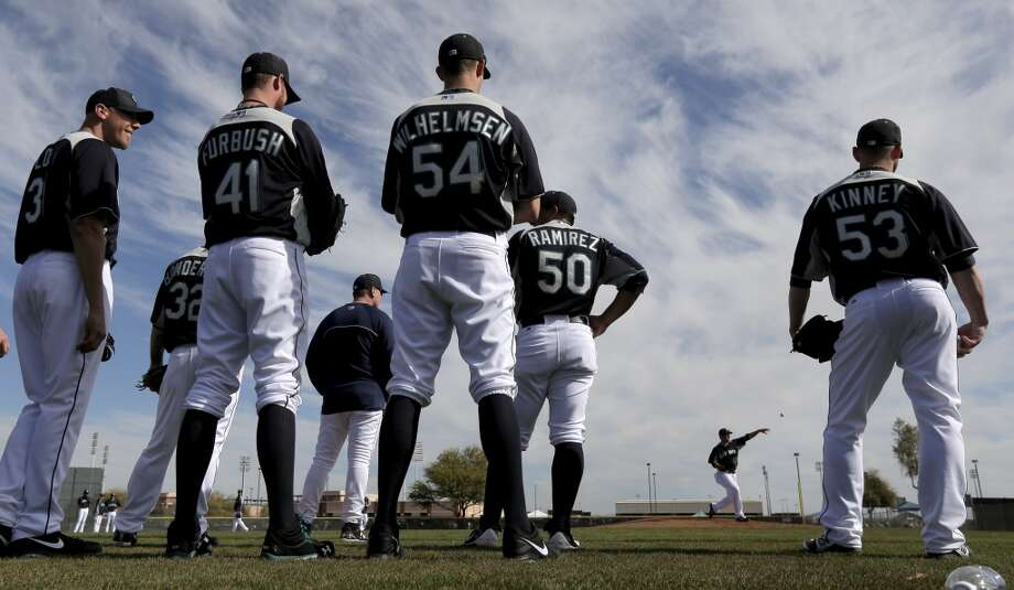 Mariners pitchers watch while fellow pitcher Joe Saunders throws during spring training Tuesday in Peoria, Ariz.