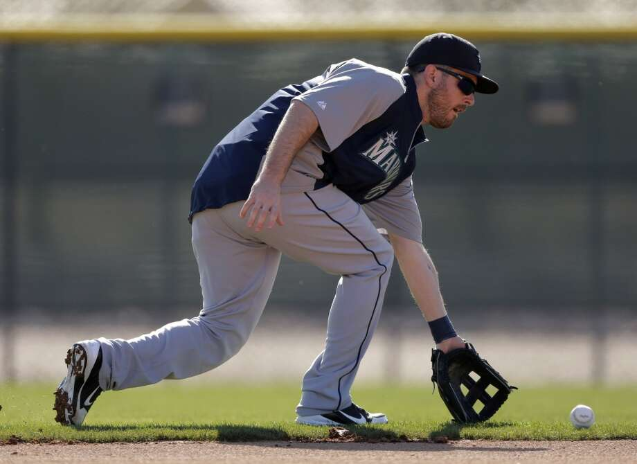 Mariners second baseman Dustin Ackley fields a ground ball during a spring training workout Monday in Peoria, Ariz.