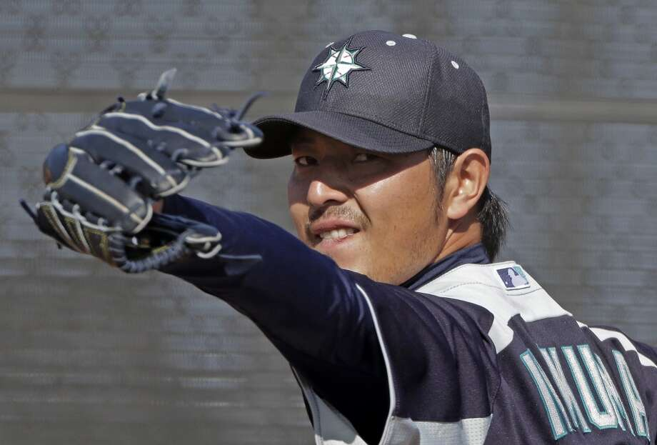 Mariners pitcher Hisashi Iwakuma throws during a spring training workout Monday in Peoria, Ariz.