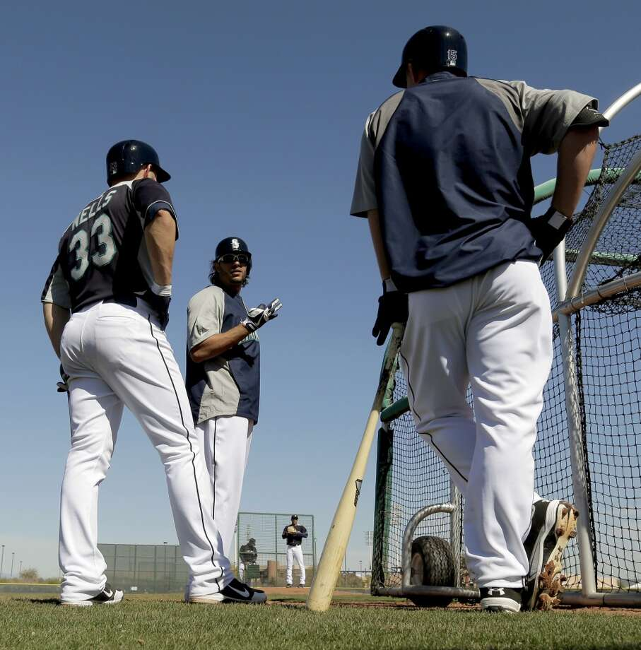 Mariners player Michael Morse (center) talks with Kyle Seager (right) and Casper Wells (33) as they wait for batting practice to begin during a spring training workout Tuesday in Peoria, Ariz.
