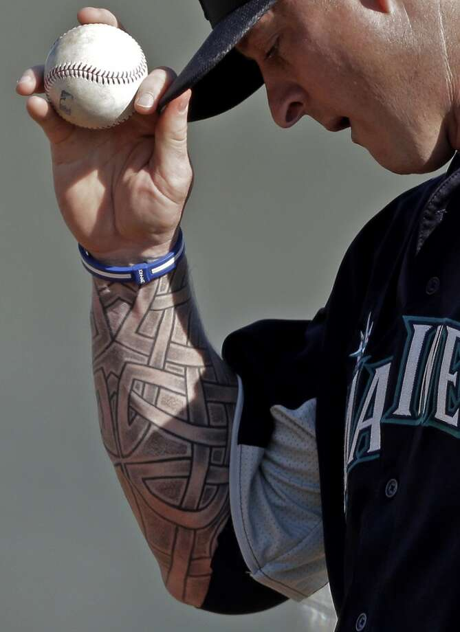 Mariners pitcher Jeremy Bonderman adjusts his hat before throwing during a spring training workout Monday in Peoria, Ariz.