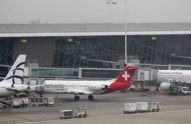Baggage carts make their way past a Helvetic Airways aircraft from which millions' of dollars worth of diamonds were stolen on the tarmac of Brussels international airport, Tuesday, Feb. 19, 2013. Eight armed and masked men made a hole in a security fence at Brussels' international airport, drove onto the tarmac and snatched millions of dollars' worth of diamonds from the hold of a Swiss-bound plane without firing a shot, authorities said Tuesday. Photo: Yves Logghe