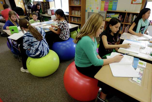 Students in Robbi Giuliano's fifth grade class sit on yoga balls as they complete their assignments at Westtown-Thornbury Elementary School Monday, Feb. 4, 2013, in West Chester, Pa.  By making the sitter work to stay balanced, the balls force muscle engagement and increased blood flow, leading to more alertness. Photo: Matt Rourke