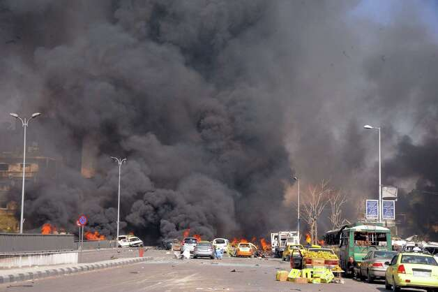This photo released by the Syrian official news agency SANA, shows flames and smoke rising from burned cars after a huge explosion that shook central Damascus, Syria, Thursday, Feb. 21, 2013. A car bomb shook central Damascus on Thursday, exploding near the headquarters of the ruling Baath party and the Russian Embassy, eyewitnesses and opposition activists said. Photo: SANA