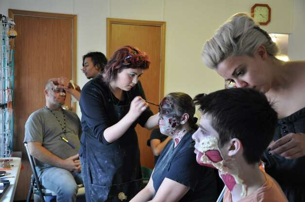 Employees of makeup company Cthululu's Den at work turning actors into zombies for  ÒThe Last Meal,Ó a zombie-themed short that was filmed in Von Ormy. Photo: Courtesy Photo