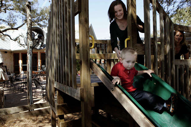 Two-year-old Alexander Brumby takes a slide down the playscape at Scenic Loop Cafe, 25615 Boerne Stage Road with help from his mother Staci. KEVIN GEIL/STAFF Photo: KEVIN GEIL, SAN ANTONIO EXPRESS-NEWS / kgeil@express-news.net
