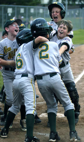 Jackson Olson (2) of the New Milford Youth Baseball/Softball Express 10-year-olds is mobbed by teammates after a home run in the state tournament, July 9, 2008 at Rogers Park in Danbury. Photo: Norm Cummings