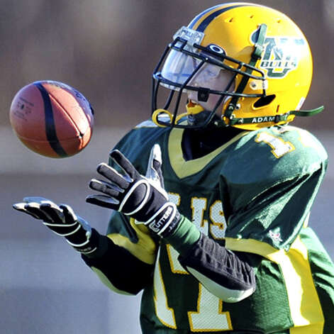 The New Milford Bulls Junior Pee Wees' Cody Madden catches a pass to start a 51-yard touchdown play during the Nov. 29, 2008 New England regional championship game against the Brookline (Mass.) Patriots at Foley Stadium in Worcester, Mass.  Courtesy of John Cheng Photo: @ 2008 John Cheng