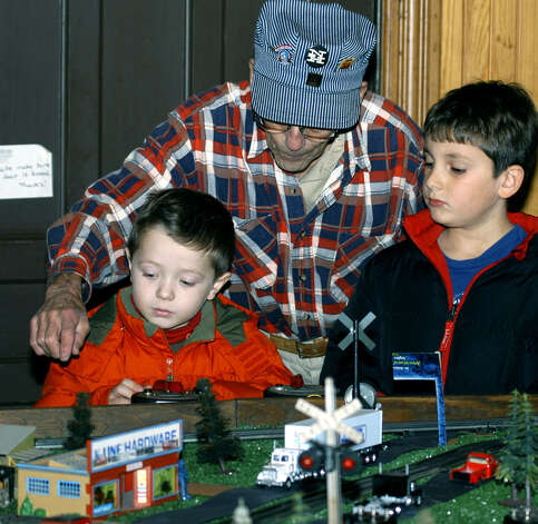 Arthur O'Connor offers Nicholas Clark, 4, left, of New York City, visiting the Clark family in Roxbury, and Ben Wiemer, 5, of New Milford some train tips. December 2007 at the railroad station train show. Photo: Deborah Rose