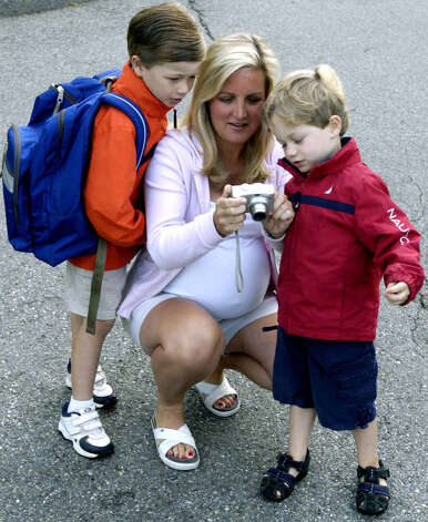 Hill and Plain kindergartner Evan Carlson, 5, left, and pre-school brother Brennan, 3, look at photographs shot by their mother, Stephanie Carlson, on the opening day of school, Aug. 27, 2008 Photo: Norm Cummings