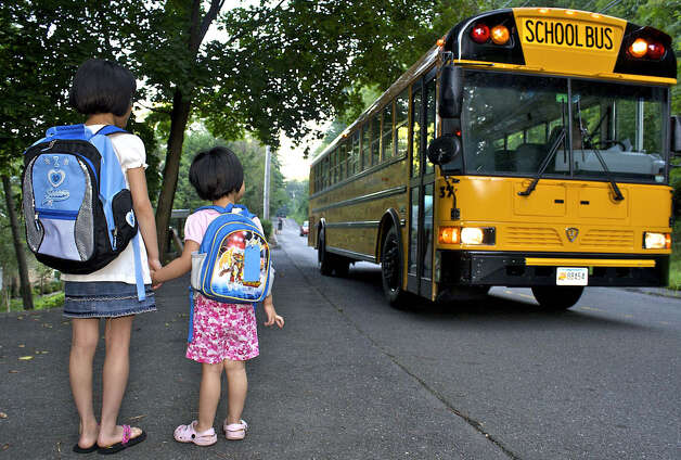 Third-grader Nova Chen, 8,  and her sister, Irene, 3, starting Excel that day, excitedly wait for their bus to stop to take them for opening day of classes at Hill and Plain School in New Milford, Aug. 26, 2009. Photo: Trish Haldin