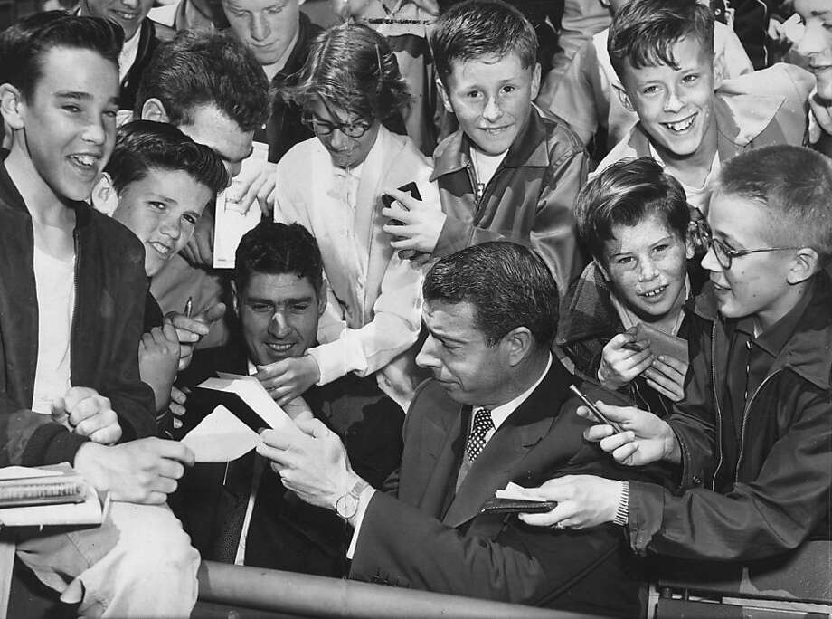 Youngsters flock around Joe DiMaggio to secure his autograph at Seals Stadium in April 1954. He was not rescued until it was time to appear at bat for three exhibition swings.  Photo: Ken Mclaughlin, STAFF