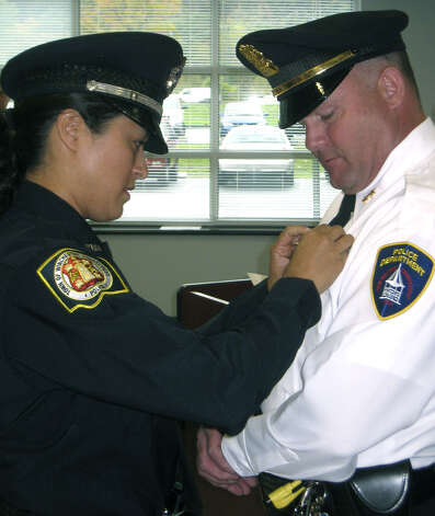The New Milford Police Department's new chief, Shawn Boyle, is pinned during a swearing in ceremony in October 2010 by Officer Kim Maher of the Winsted Police Department, the day before the couple was to be wed. Photo: Norm Cummings