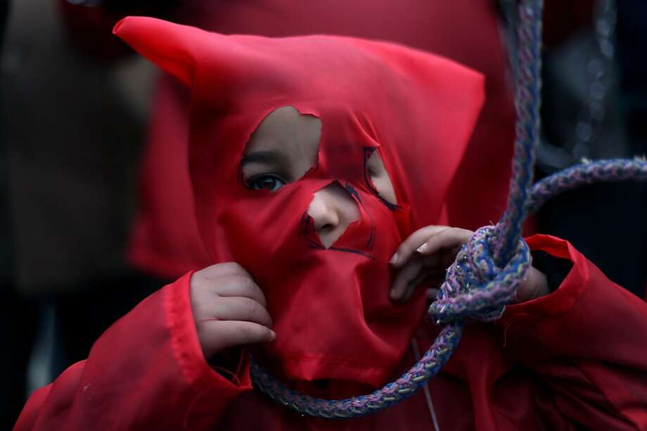 Disturbing costume:A child wears a red hood and a noose during an anti-government protest in front of Egypt's high court building in Cairo. Photo: Khalil Hamra, Associated Press
