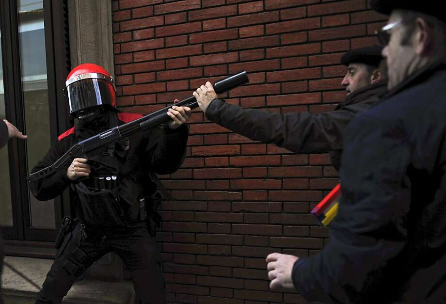Not the smartest way to confront a riot cop: Spaniards protest government austerity measures and political corruption in front the regional Parliament in Pamplona. Photo: Alvaro Barrientos, Associated Press