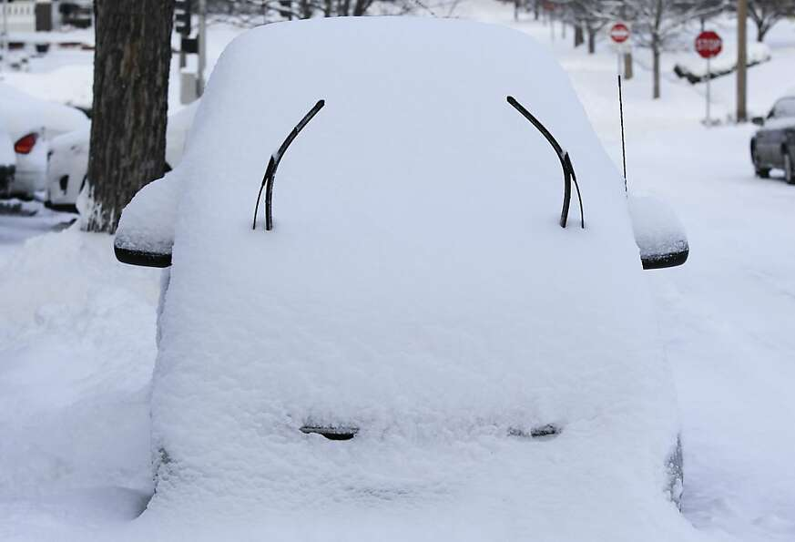 Raised wipers and a snow-covered hood give a car a quizzical expression in Omaha, Neb.