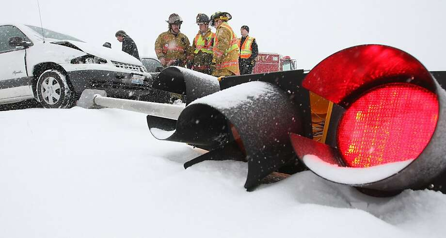 Takes a licking, keeps on flickering: In Alton, Ill., firefighters examine a traffic signal that was knocked down during an accident in a snowstorm, but is still working. Photo: John Badman, Associated Press
