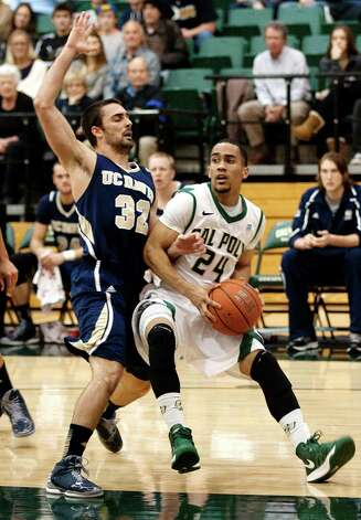 UC Davis' Paolo Mancasola (32) guards Cal Poly's Jamal Johnson (24) during the first half of their NCAA college basketball game, Saturday, Feb. 9, 2013, in San Luis Obispo, Calif. (AP Photo/The Tribune (of San Luis Obispo), Laura Dickinson) Photo: Laura Dickinson, Associated Press / The Tribune (of San Luis Obispo)